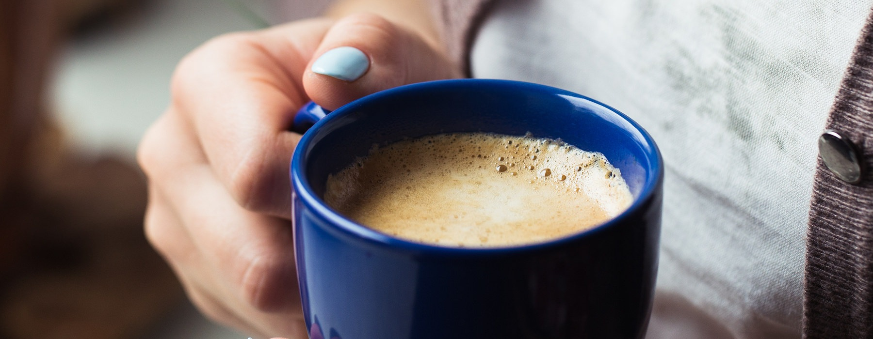 close up of a woman's hand holding a mug of coffee